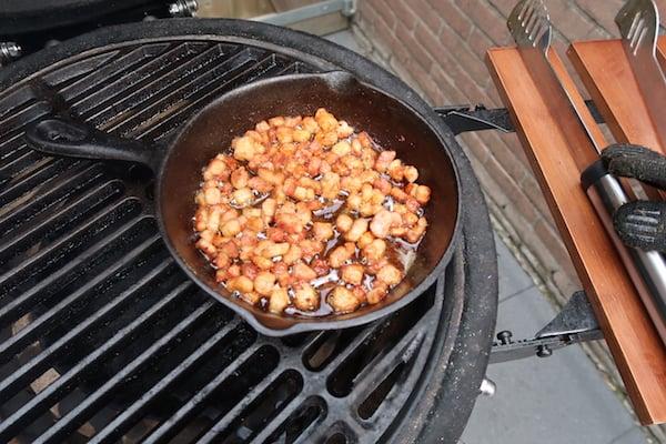 Uitgebakken spekjes in een skillet op de Barbecue